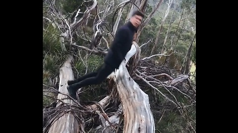 Guy Does A Flip Over A Log With Hands In His Pocket
