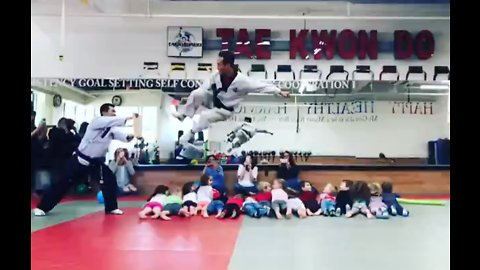 Tae Kwon Do master leaps over 16 children to break board