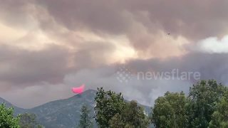 Cloud of red fire retardant hovers over mountain in Holy Fire fight - Video