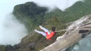 Cleaners abseil to pick up rubbish from cliff under glass bridge - Video