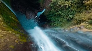 DRONE FLIES THROUGH SPECTACULAR WATERFALL IN JUNGLE CANYON