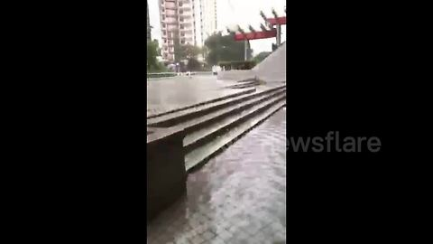 Resident walks on flooded pavement in Hong Kong in aftermath of Typhoon Mangkhut