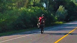 Motorcyclist casually rides down highway on back wheel