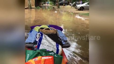 Man pushes belongings on kayak in flooded France campsite
