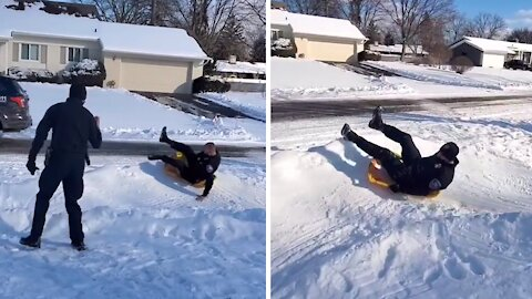 Police officers join kids to go sledding down hill