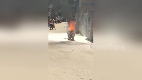 Villagers desperately try and fail to extinguish moped fire