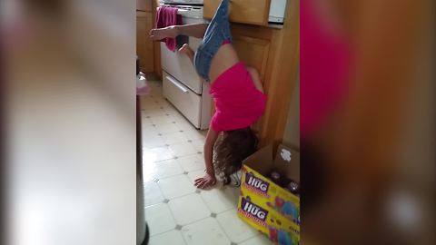 Little Girl Hangs By Her Shorts On Drawer Handle