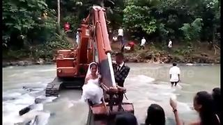 Over the threshold: Newlyweds carried across floods in digger