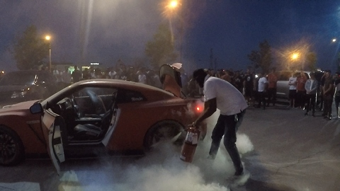 Crowd cheers as masked hero extingishes supercar that caught on fire