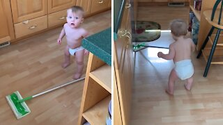 Adorable baby helps clean around the house