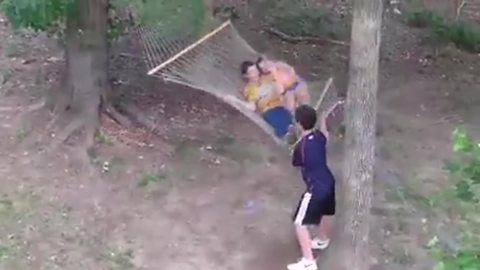 A Young Boy Jumps On A Swinging Hammock But Falls Out The Other Side
