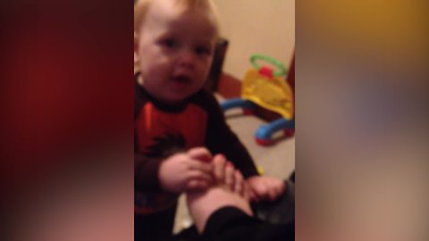 A Tot Boy Like To Chew On His Mom's Toes