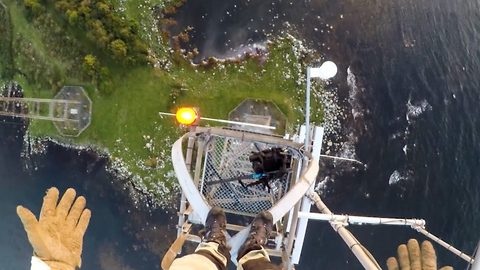 Daredevil climber gives thrill seekers a birds eye view as he scales a 140m mast