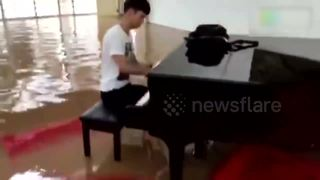University student plays piano in flooded hall - Video