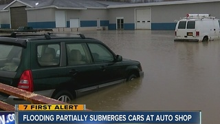 Flooded creek spills into auto shop parking lot - Video