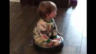 Toddler Hitches a Ride on a Roomba