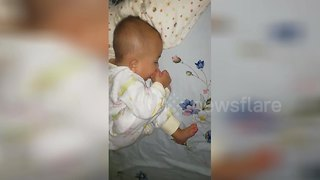 Adorable baby licks toes while sleeping - Video