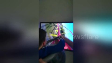 Boy enjoys a thrilling ride made from of a washing basket and big-screen TV