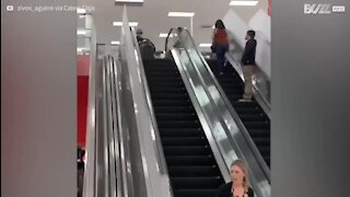 Kid slides off escalators in a sledge!