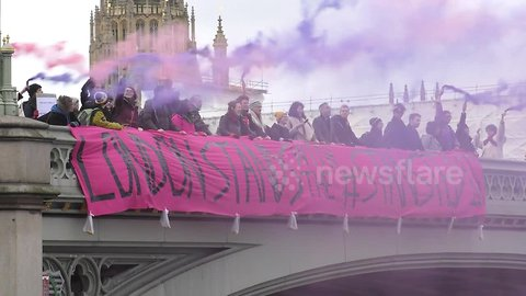 Protesters drop banner from Westminster Bridge in support of Stansted 15