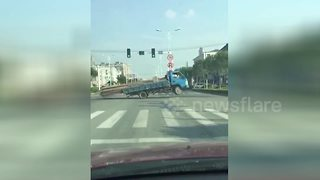 Overloaded lorry seesaws onto its back wheels