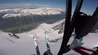 Brave skier performs awesome parachute jump