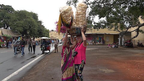 Kindly vendor in India trusts Canadian tourist to carry her papadums