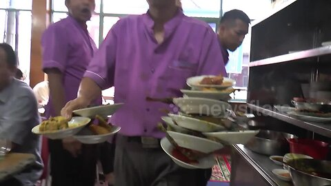 Talented waiter carries 17 food-filled plates at once in an Indonesian restaurant