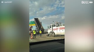 Truck stuck after colliding with overhead highway signs
