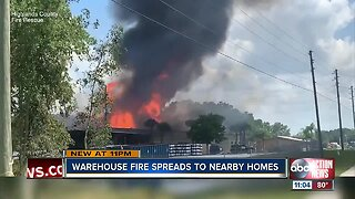 Warehouse fire spreads to nearby homes