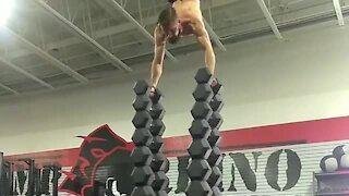 Athlete performs insane workout atop dumbbell tower