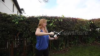 Woman shows how to open a bottle of champagne with a hatchet