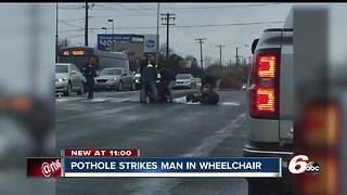 Man in mechanical wheelchair hits pothole - Video
