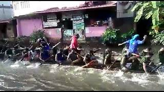 Indian club practices for boat race on flooded road in town