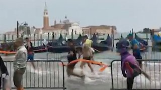 Venice marathon runners don't let the flooding hold them back as they race through ankle-deep water