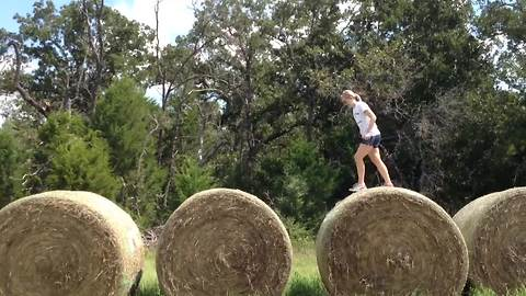 A Teen Girl Runs Across Large Bales Of Hay But Fail To Finish Her Race