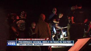 Fisherman hooks, reels in man in water - Video