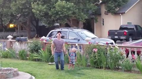 A Young Man And A Tot Boy Play Watermelon Throw Game