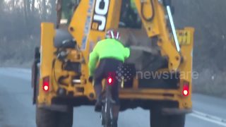 Cyclist holds onto excavator to get uphill - Video