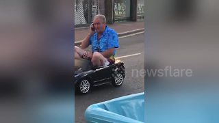 Hilarious moment man drives through UK town in toy car - Video