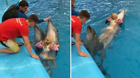 Fearless three-year-old girl rides on top of fast-swimming dolphin
