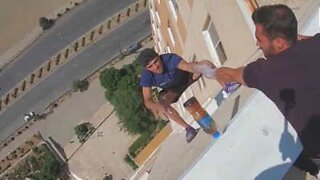 """Young man does """"bottle flip challenge"""" hanging from building"""