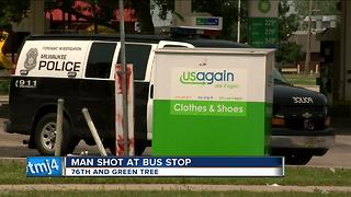 Man shot at bus stop by passing car - Video