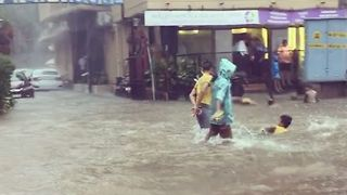 Kids Splash About and Swim on Flooded Mumbai Street - Video