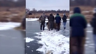 Extreme cold forces villagers to move hay bales across frozen river - Video