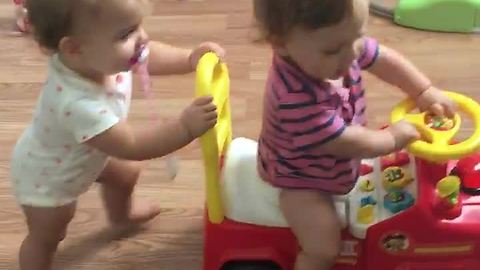 Baby preciously pushes twin sibling in toy car