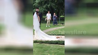 Where was my invite? Cat hitches ride on bride's wedding dress