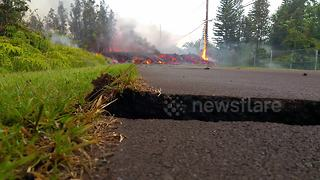 Volcanic lava crosses road in Hawaii and burns electricity pole