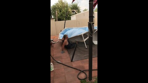 Man struggles to hold down pool during extremely strong winds