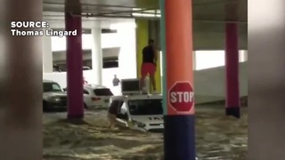 Man stranded on taxi during flooding - Video